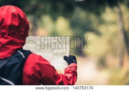 Woman hiker hiking walking in dark autumn forest. Young female looking at map and planning trip or get lost on trail in fall woods. Magical inspirational forest landscape background.