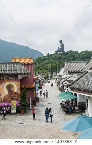 HONG KONG - MAY 26: Tourists walk around Ngong Ping village with Tian Tan Buddha as background on May 26 2016 in Hong Kong.