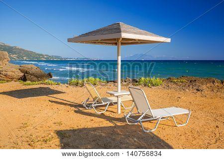 Parasol and deckhcair on the Banana Beach of Zakynthos island, Greece