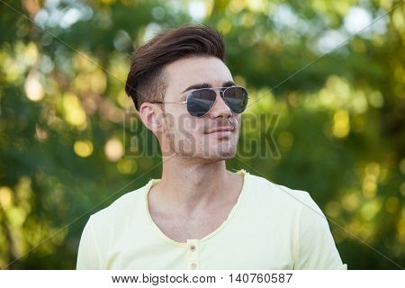 Attractive guy in the park with sunglasses and yellow t-shirt