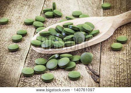 Spirulina,chlorella supplement pills in wooden spoon .