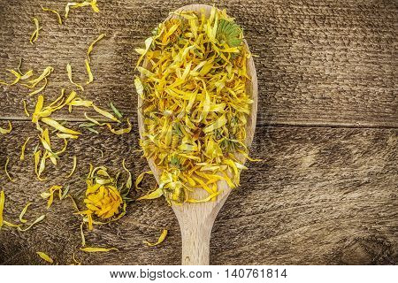 Dry yellow calendula on wooden table .