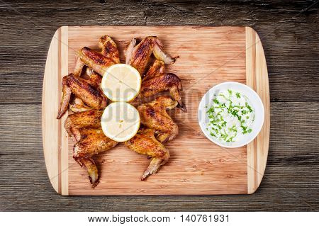 delicious grilled chicken wings with garlic sauce, lemon on a cutting board on wooden rustic background, top view