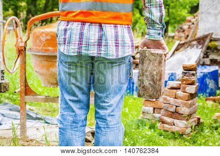 Construction worker with brick near concrete mixer