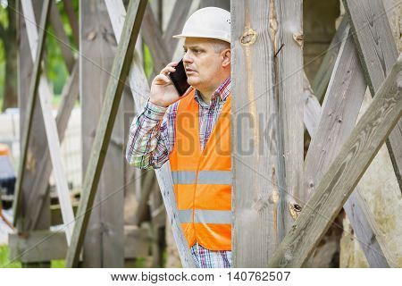 Construction worker looking through scaffolding in summer day