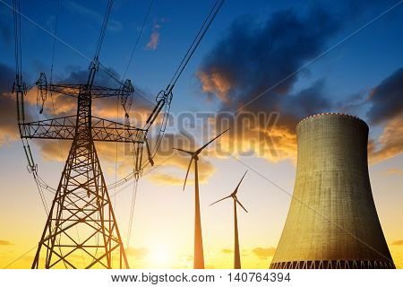 Nuclear power plant with wind turbines and electricity pylon in the sunset. Energy resources concept.