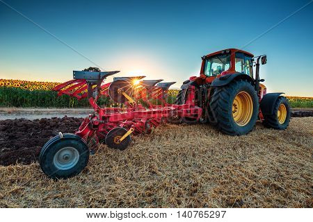 Farmer In Tractor Preparing Land With Cultivator