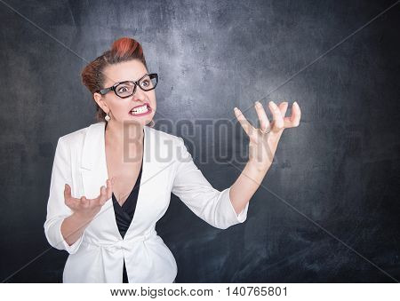 Angry Teacher In Glasses On Blackboard Background