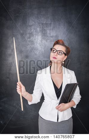 Teacher Looking On Something Up On The Blackboard Background