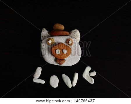a piglet muzzle from pebbles on a black background. funny and kind