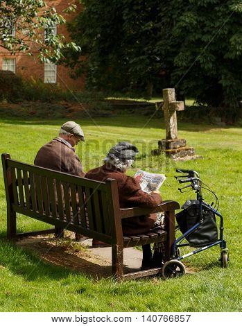 SOUTHWELL ENGLAND - JULY 31: An elderly couple (manwoman) relaxing on a bench in the graveyard of Southwell Minster. In Southwell Nottinghamshire England. On 31st July 2016.