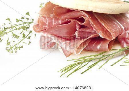 Italian prosciutto crudo raw ham leg sliced on white