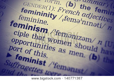Feminism word in English dictionary. Close-up shot.