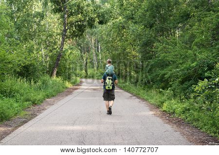 Father and daughter in the summer forest. They are walking along the road. She is sitting on his shoulders. He is also holding a rucksack.
