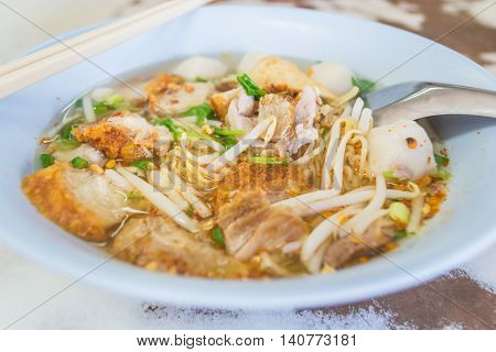 Spicy Thai Tomyum noodle with streaky pork vegetable and balls in a blue bowl.