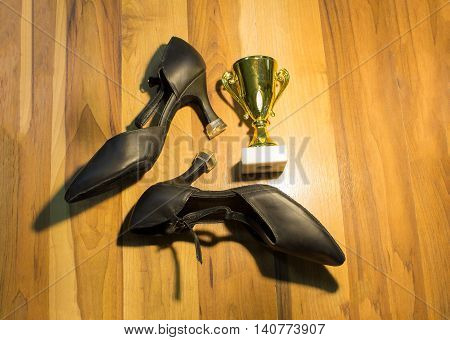 The black dance shoes on wooden floor background and golden cup of winner