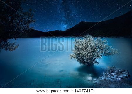night deep dark blue. Milky way stars over mountain lake. Magic scenic landscape
