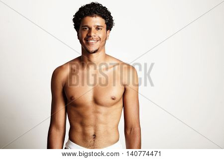 Young Smiling Man Topless On A White Wall