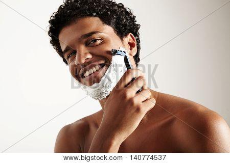 closeup portrait of shaving man looking at camera