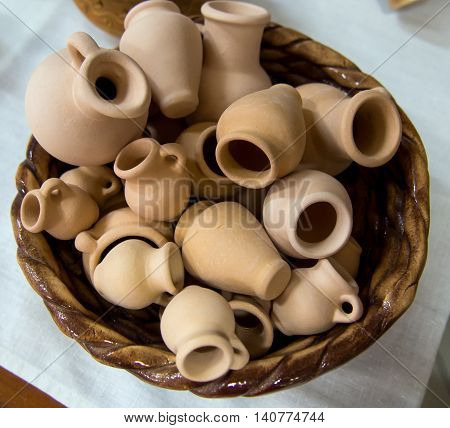 Small souvenir clay pots in a wicker basket