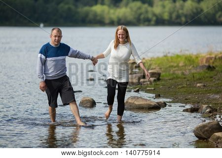 Young couple goes for the hand on the river. Honeymoon.
