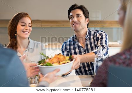 Man passing food bowl with roasted chicken to his friend. Happy smiling man eating with his friends at home.Young friend socializing after a long time.
