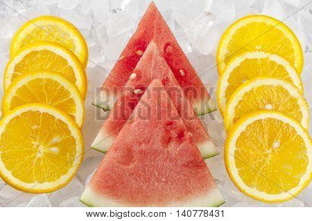 Watermelon slices between orange slices. Rows of orange slices and watermelon wedges stacked up on ice.