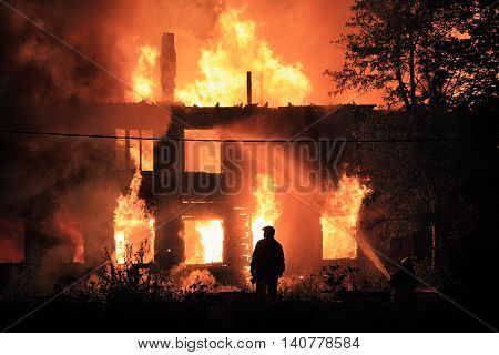 dark firefighters silhouette on house fire background