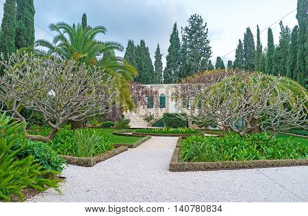 The stone residential mansion surrounded by the lush garden with flower beds and spreading trees Haifa Israel.