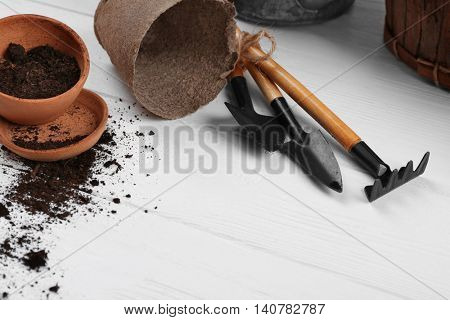 Gardening tools and flowerpots on wooden background