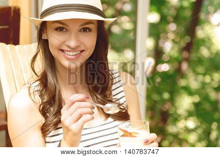Unforgettable taste. Portrait of pleasant beautiful delighted woman holding spoon and eating a dessert while smiling