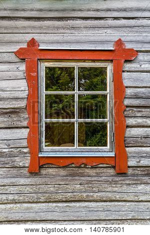 One window with red frames on log house wall, traditional style.