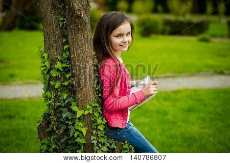 Pretty little girl poetess in jeans and jacket with long brunette hair holding notebook and pen standing near tree with green creeper vine on grass