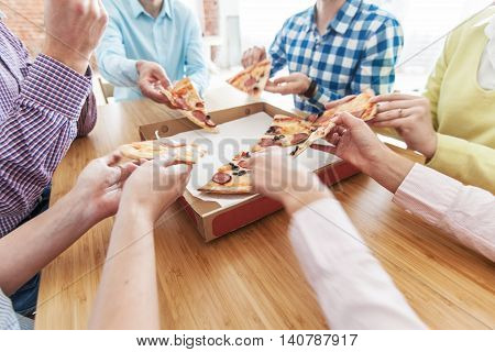 Friends hands taking slices of pizza close up