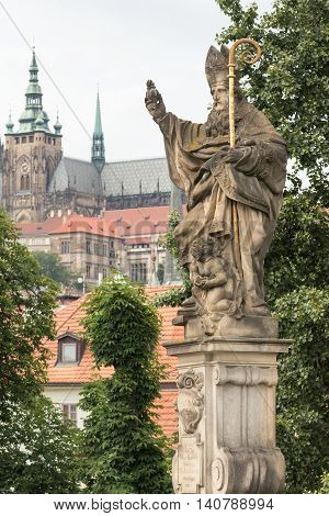 Statue of St. Augustine on Charles Bridge in Prague. The statue was created in 1708. St. Vitus Cathedral is in the background.