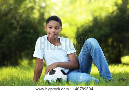 African American boy with soccer ball in park