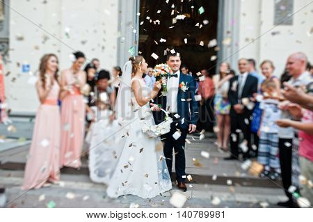 Wedding Couple Come Out From Church Under Petals Of Roses. Blur Effect