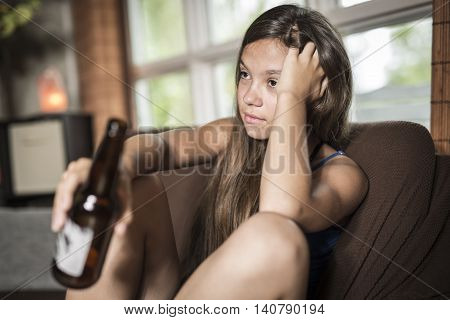 A sadness teen girl sits on sofa at home with beer