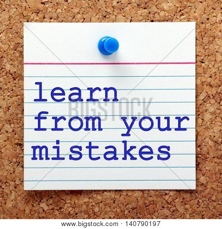 The words Learn From Your Mistakes in blue txt on a note card pinned to a cork notice board as a reminder