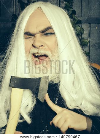 Bearded senior man in long white wig with axe on wooden background