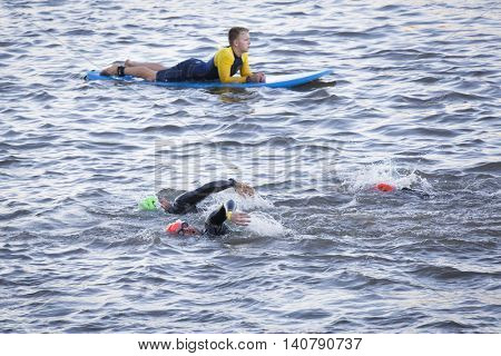 NEW YORK -?? JUL 24 2016: Lifeguards on surfboards patrol the route as athletes compete in the NYC Triathlon Race in New York. The swim portion is 1.5 kilometers in the Hudson River at Riverside Park.