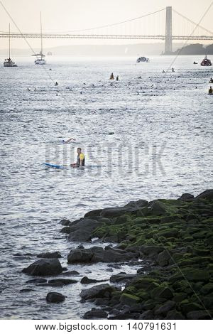 NEW YORK â?? JUL 24 2016: Lifeguards on surfboards patrol the route as athletes compete in the NYC Triathlon Race in New York. The swim portion is 1.5 kilometers in the Hudson River at Riverside Park.