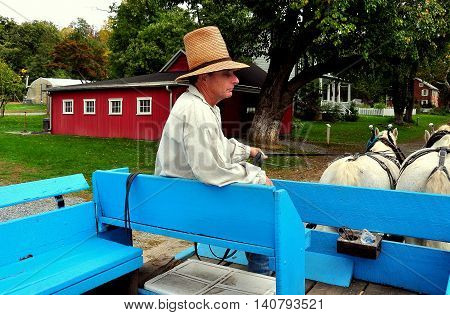 Lancaster Pennsylvania - October 14 2015: Wagon Driver in high straw hat with his team of two white horses at the Landis Valley Village and Farm Museum