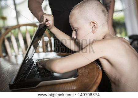A boy with internet dependence playing with keyboard being dragged by mother from her computer