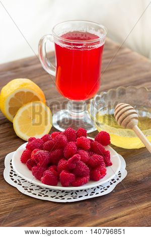 Hot tea with lemon honey and raspberries. Home treatment for colds and flu.