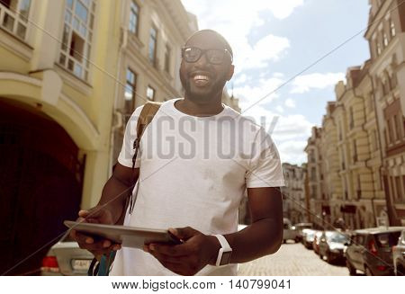 With positivity in mind. Cheerful handsome delighted man smiling and holding tablet while walking along the street