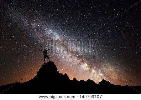 Landscape with Milky Way. Colorful night sky with stars and silhouette of a happy sporty man and raised up arms on the top of mountain. High Rocks. Background with galaxy and silhouette of a man.