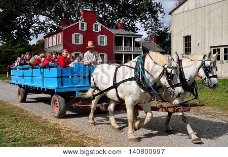 Lancaster Pennsylvania - October 14 2015: School children riding in a wagon pulled by two white horses at the Landis Valley Village and Farm Museum