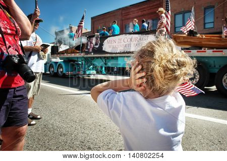 KALISPELL, MT, USA - JULY 4: Girl covers ears after a loud boom during 4th of July Parade in Kalispell, Montana, on July 4, 2016.