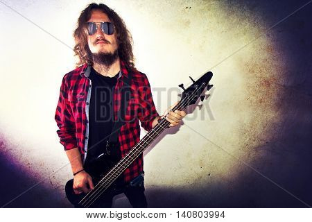 Guitarist playing bass guitar. Retro instagram vintage grunge picture.